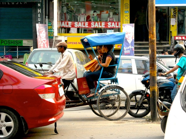 Two women being driven by a rickshaw driver.